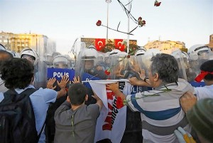 Protesters scuffle and throw flowers at riot police at Taksim Square in Istanbul